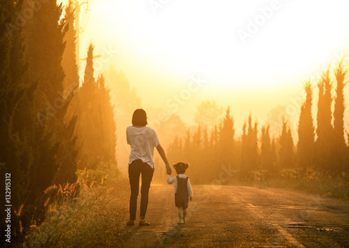Obraz na plátne  Mother and child holding hands at sunset with copy space, view f