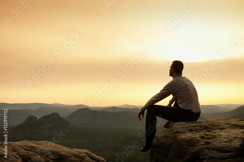 Fototapety, obrazy: Adult hiker in black sit on mountain  edge. Man enjoying evening