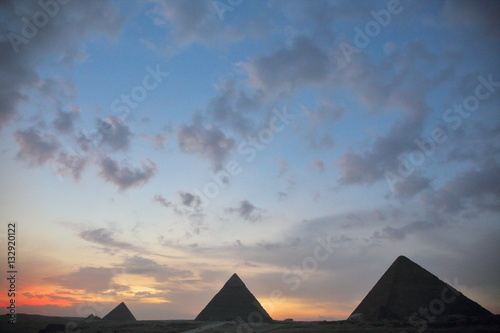 Egypt Dramatic sunset behind distant Egyptian pyramids in Giza, Cairo, Egypt