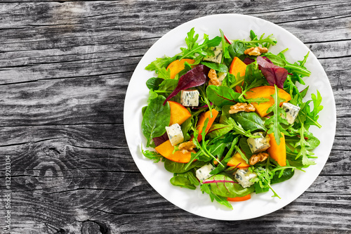 Fotografía  persimmon salad with lettuce leaves, blue cheese and walnuts