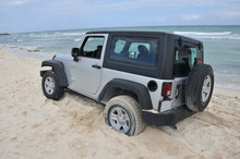 A Silver Off Road Vehicle Stuck In The Sand In Cancun, Mexico.