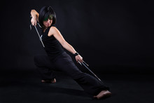 Young Woman In Fighting Stance Holding A Pair Of Sai: Studio Portrait On Black Background