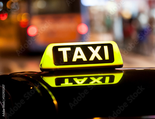 Zdjęcie XXL Taxi znak na dachu taxi samochód przy nocy ulicą