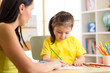 Woman teaching kid to write. Elementary pupil painting with teacher