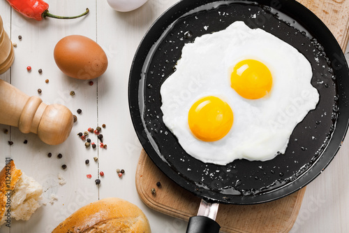 Foto op Aluminium Gebakken Eieren Healthy quick breakfast made of two fried eggs on a table. Traditional simple food on a frying pan for eating. Top view.