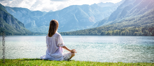 Tuinposter Ontspanning Woman meditating at the lake