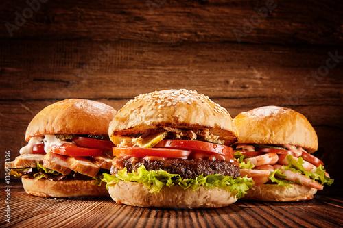 trzy-duze-hamburgery-z-kurczaka-wolowiny-i-krewetek-na-brazowym-drewnianym-tle