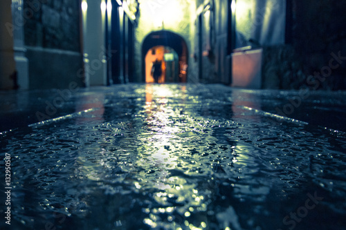 Canvas Prints Narrow alley Focus on wet ground along dark medieval alley on a rainy night, Butter Slip, Kilkenny Ireland.