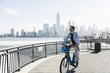 USA, man on bicycle at New Jersey waterfront with view to Manhattan