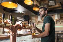Bartender In Coffee Shop Pouring Beer From Tap