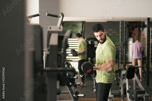 Young man training biceps in gym