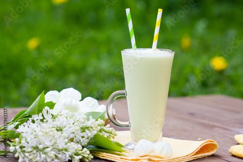 Foto op Plexiglas Milkshake milkshake in a glass beaker with a straw in the open air