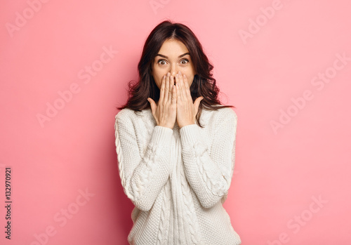 Fotografia  Portrait of amazed young woman over pink background