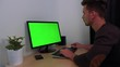 A young, handsome man types on a computer with a green screen