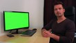 A young, handsome man sits at a desk in front of a green computer screen and explains something to the camera