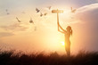Woman holds a sign with word faith and flying birds on nature sunset