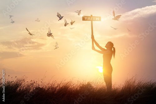 Canvas Print - Woman holds a sign with word faith and flying birds on nature sunset