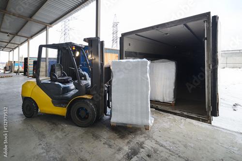 Fototapeta Wózek widłowy w magazynowym ładowania pudełku w samochód outdoors