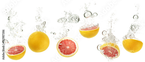 set of grapefruits dropping into water on white background