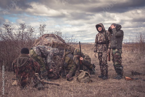 Foto op Canvas Jacht Hunters preparing for team hunting in rural field with hunting tent in overcast day