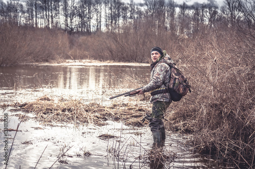 Foto op Canvas Jacht hunter man creeping in swamp during spring hunting season