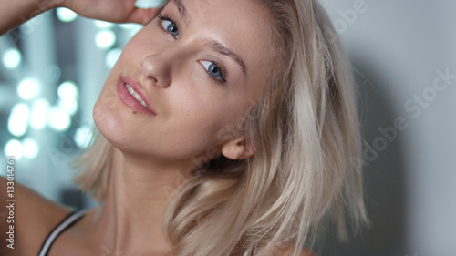 Valokuva  Portrait of playful attractive young woman over shining background