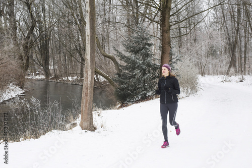 Fotobehang Wintersporten Mid adult woman jogging on water's edge in winter