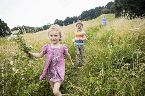 Children playing in grassy landscape - 133029524
