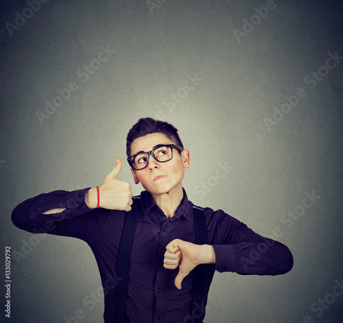 Photo Perplexed man with thumbs down thumbs up gesture looking up