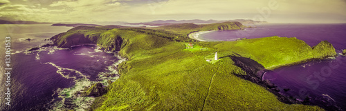 Foto op Plexiglas Aubergine Surreal aerial landscape of ocean, land, and lighthouse in vivid green and purple colors