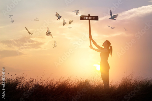 Canvas Print - Woman holds a sign with word hope above head while chanting and praying