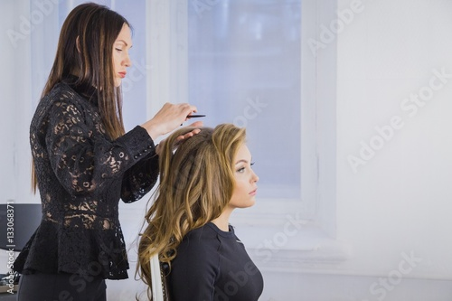 Professional hairdresser doing hairstyle for young pretty woman with long hair
