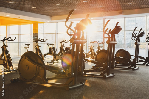 Poster Fitness Modern gym interior with equipment, fitness exercise elliptical trainers