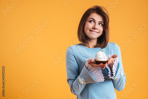 Cuadros en Lienzo Pensive smiling young woman holding cupcake and thinnking