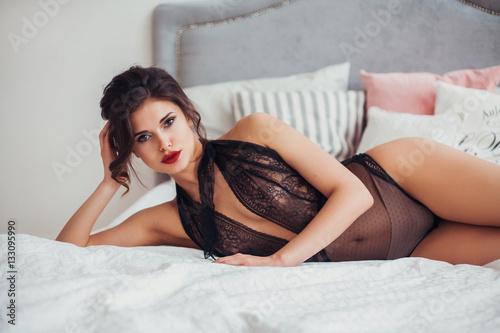 Fotografie, Obraz  Beautiful sexy woman wearing seductive black lingerie posing in bedroom
