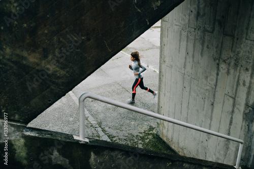 Plakat Sporty kobieta bieg na zima deszczowym dniu. Miastowa żeńska atleta ćwiczy na asfalcie.