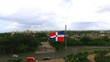 The camera flies over a large area against the background of growing the Dominican Republic flag
