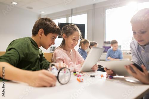Fotografía  kids with tablet pc programming at robotics school