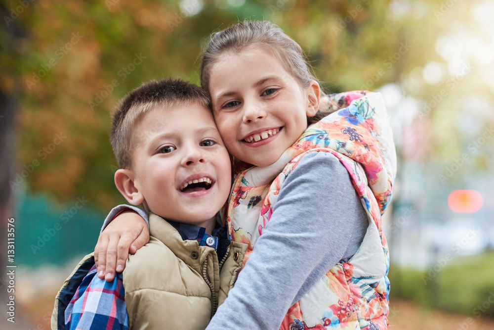 Fototapety, obrazy: Happy siblings hugging outside