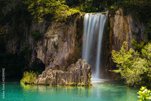 Fototapeta Waterfall and a lake with a stone in the Plitvice Lakes National Park.