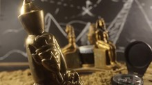 Pharaoh Statues On A Sand Video. Video Of A Golden Pharaoh Statues With Sand And Compass Laying On Archeology Table With Black Board Drawn Pyramids On A Background.