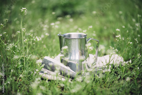 Fotografie, Obraz Frothing milk pitcher on the cloth napkin outdoors on the green grass background