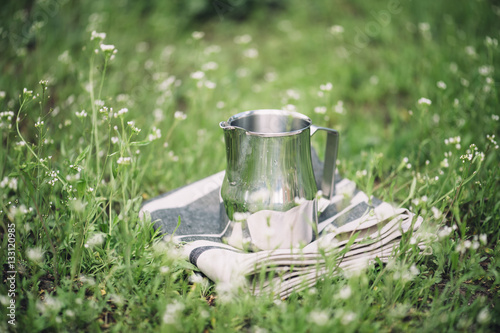 Fototapeta Frothing milk pitcher on the cloth napkin outdoors on the green grass background