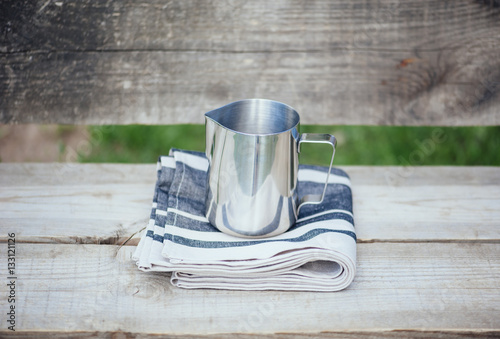 Fototapeta Frothing milk pitcher on the cloth napkin on the wooden background