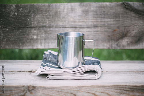 Fotografie, Obraz Frothing milk pitcher on the cloth napkin on the wooden background