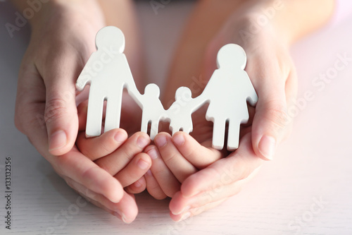 Child and adult person holding figure in shape of happy family, closeup Wallpaper Mural