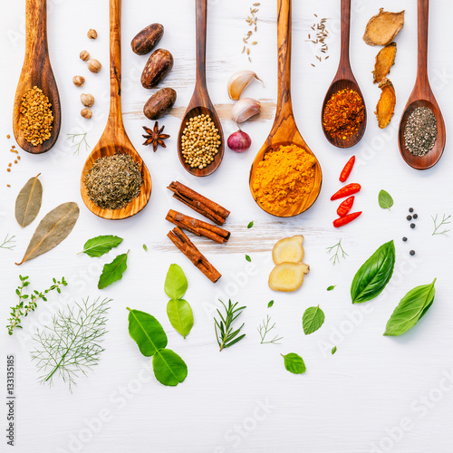 Poster Spices Various herbs and spices in wooden spoons. Flat lay of spices in