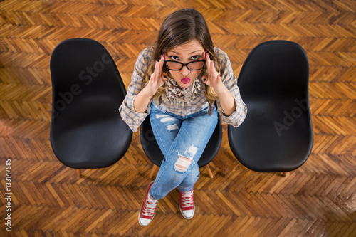 Fotografering  Portrait of modern young businesswoman sitting on the chair in her office and ma