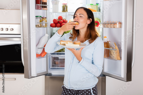 Fotografija Woman Eating Sweet Food Near Refrigerator
