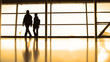 Passengers in front of window in airport, silhouette, warm